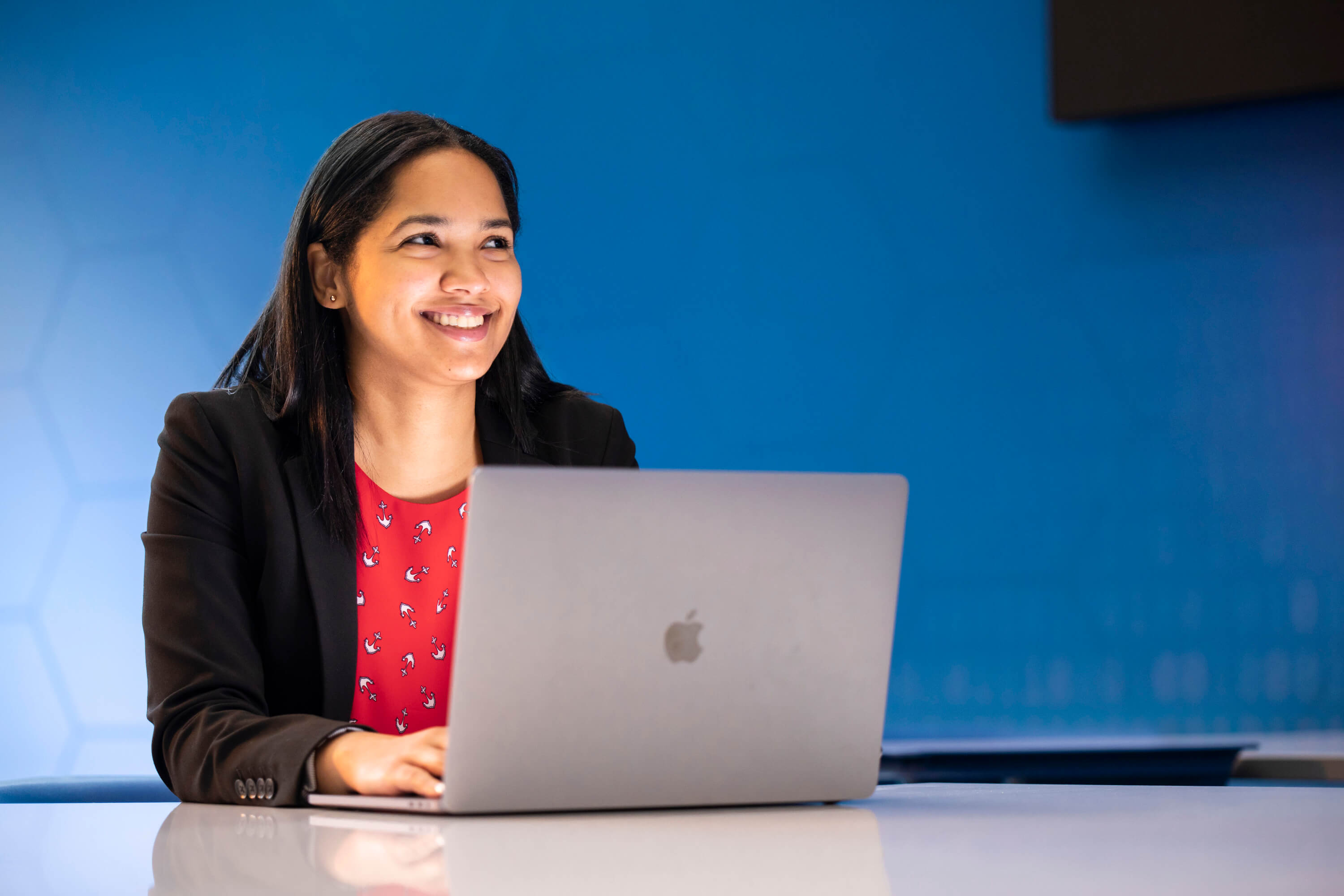 Woman at desk in front of laptop