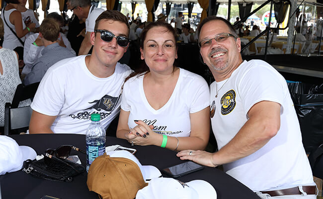 A family of three enjoys Family Weekend Tailgate at UCF