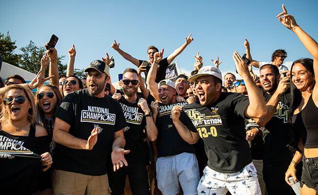 A large group of UCF fans cheering and showing their Knight spirit